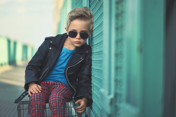 A Child rebel. A boy, 5 years old, fashionably dressed, poses like a model on the bridge. He is wearing a black leather jacket, red pants and sunglasses.
