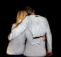 Couple in love hug each other against a black background