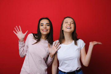 Portrait of a two amazing girls having fun laughing against a red wall in studio.