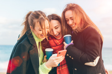 Three young happy girls watching smartphone and laughing - group of friends drinking coffee to go and having fun together