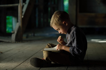 A boy in an old house reading a mysterious book. Fun in search of treasure.
