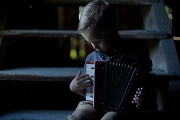 A boy plays the accordion in the old house, the mysterious scenery, the photo on the cover of the book