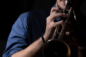 A person in a blue shirt playing a silver plated trumpet in a dark environment