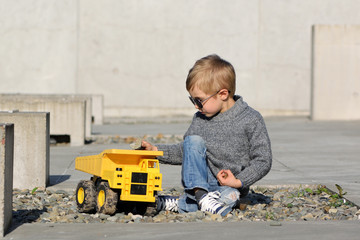 A four years old smiling boy in sunglasses playing a yellow track on concrete background.