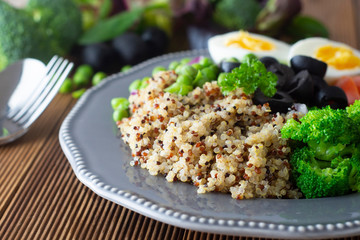 Quinoa salad with green pea,broccoli, olives. Healthy food, lunch over wooden background. Vegetarian food, snack.