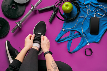 Young woman laces sneakers, preparing for training. Bottle of water, yoga mat, phone, headphones on purple background flat lay top view.