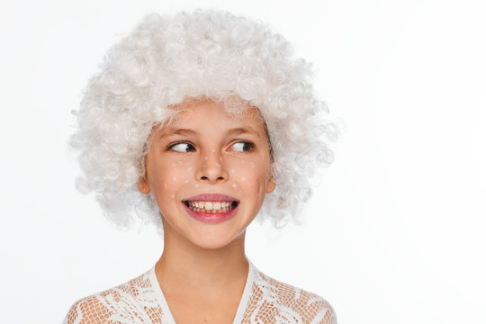 Portrait of a cheerful, energetic eight-year-old girl in a white wig and with white freckles