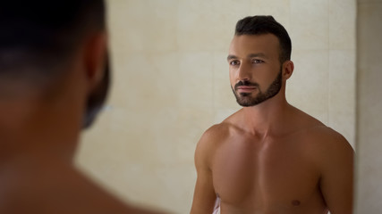 Bearded handsome man looking in mirror, perfect body, daily workout result