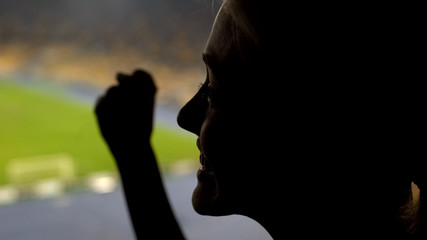 Happy woman fan cheering for football team winning on crowded stadium, emotion
