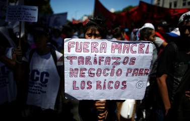 "A demonstrator holds a banner that reads ""Macri out. High rates are business for rich people"", during a protest against the increase of public rates, in Buenos Aires"