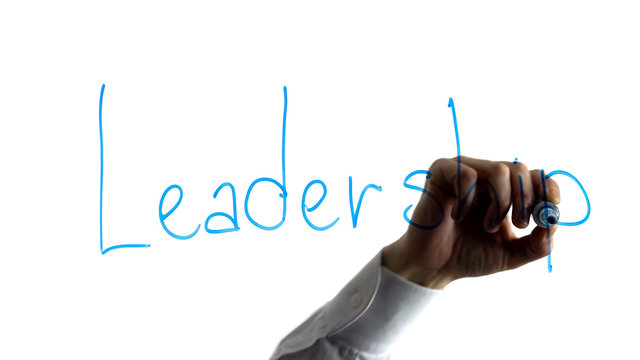 Businessman writing leadership word on white board, team building and motivation