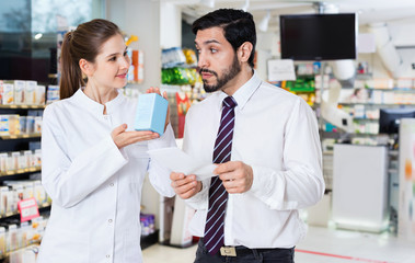 Woman pharmacist is recommending medicine for man client in apothecary.