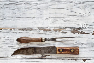 Antique meat fork and butcher's knife over top a rustic white wood table / background. Image shot from overhead view.