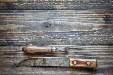 Antique meat fork and butcher's knife over top a rustic wood table / background. Image shot from overhead view.