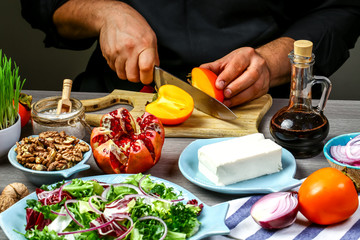 Chef hands cooking Tasty Persimmon salad with arugula, nuts, feta cheese, Fitness food. Superfoods