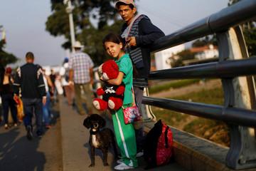 A Venezuelan family cross the Colombian-Venezuelan border over the Simon Bolivar International Bridge on the outskirts of Cucuta