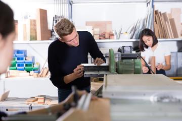 Architect polishing elements of model on sanding machine