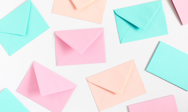 Different colored envelopes on white background. Flat lay, top view, copy space