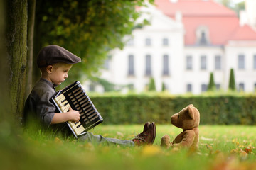 A four years old boy sitting on grass and play accordion for teddy bear
