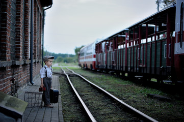 Four-year-old sad boy, dressed in retro style, is standing  on the platform and looks at the train