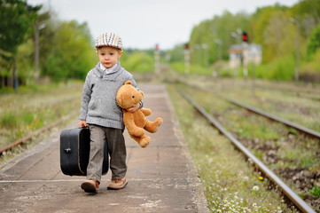 Little boy goes with a suitcase and a teddy bear at the train station