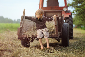The child helps parents on the field at haymaking. Summer and field work in the countryside.