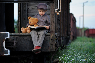 Little boy traveler is  sitting on the wagon with a teddy bear and reading a book.