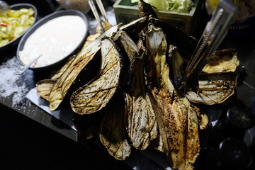 Grilled eggplants cut in half on a table for a catering, top view.