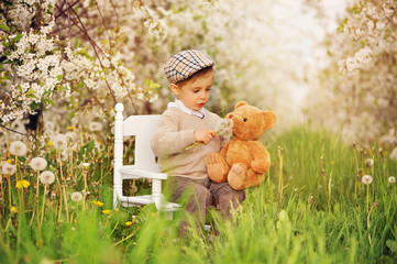 A little boy with a teddy bear in a blooming cherry orchard. Child and spring. A teddy bear smelling the flowers.