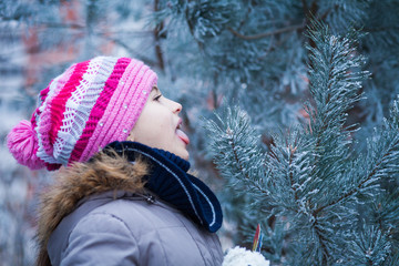 girl in colorful hat licks the frost from the needles of a pine