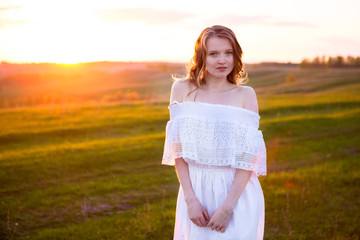 Cute young blonde woman in in green field at summer or spring sunset