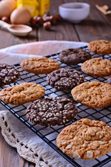 Thin, tasty, crunchy chocolate and caramel cookies on a black metal grid, vertical