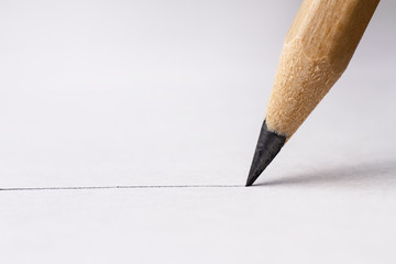Close up of pencil with drawing line on textured white paper