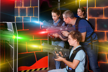 positive young parents and children with laser pistols playing l