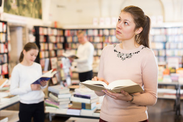 Portrait of happy woman standing with open book