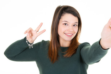 Young woman in green sweater making selfie and showing peace gesture
