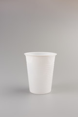Round white Plastic Cup isolated on grey background