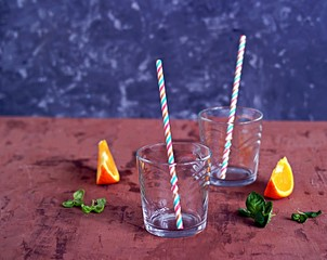 Glass glass with straw prepared for a refreshing orange cocktail.