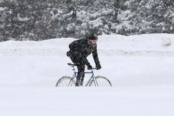 A man bikes during a winter snow storm in Ottawa