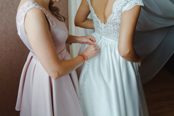 A girl dresses a bride in a white wedding dress.