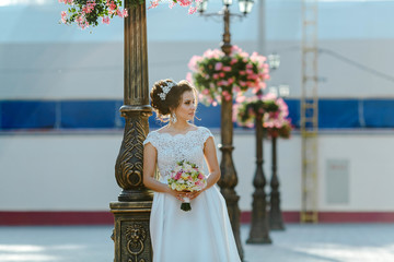 Portrait of a beautiful bride near a lantern decorated with flowers.