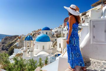Elegante Touristin in blauem Kleid genießt die Aussicht auf die weißen Häuser und blauen Dächer des Dorfes Oia auf Santorini, Kykladen, Griechenland