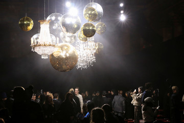 A woman takes a picture of chandeliers arranged at the Michael Kors collection during New York Fashion Week in New York