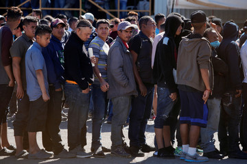 Migrants line up for food at a provisional shelter in Piedras Negras
