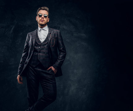 A stylish man dressed in an elegant suit with sunglasses posing with a hand in a pocket against a dark textured wall