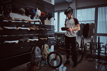 Teenage BMX rider standing with his bike, choosing new sneakers in a shop.