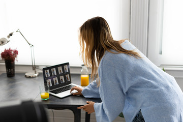 Young woman looking at photos on laptop