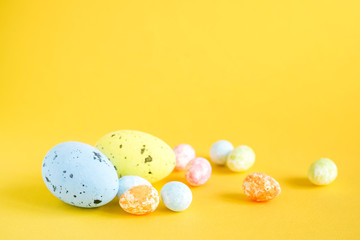 Bright Easter decorative eggs on a yellow background, close up, soft focus. Easter background