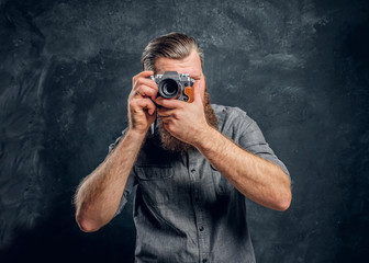 A bearded photographer wearing a gray shirt takes a photo. Studio shot on a gray textured wall