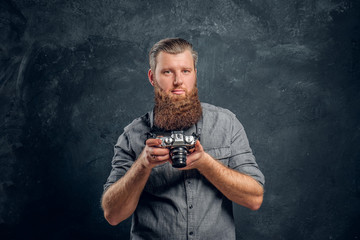 A man with a stylish haircut and beard wearing a gray shirt holding a photo camera. Studio shot on a gray textured wall